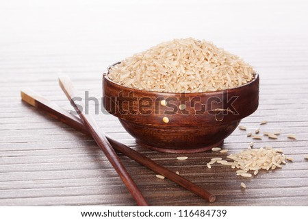 Luxurious rice background. Raw brown natural rice in round wooden asian bowl on brown background. Culinary asian eating. - stock photo