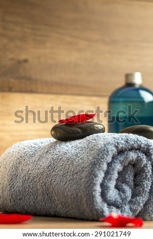 Luxurious spa arrangement with a a blue folded soft towel, black massage stone with red rose petal on top and a bottle of massage oil or moisturizing lotion. - stock photo