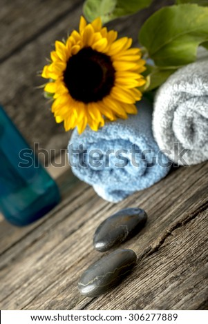 Luxurious spa setting for a couple with a folded soft towels with sunflower on top, black massage stones, and a bottle of massage oil or moisturizing lotion, inviting you to enjoy a relaxing massage. - stock photo
