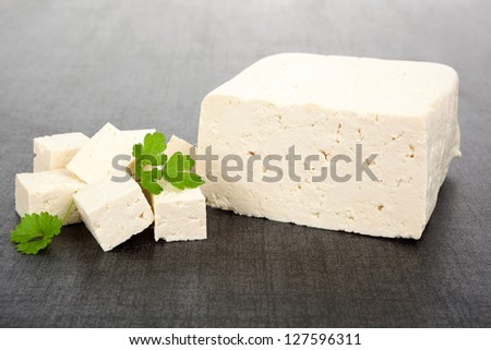 Luxurious tofu background. Tofu piece, cubes and fresh parsley isolated on dark background. Culinary vegan and vegetarian eating. - stock photo