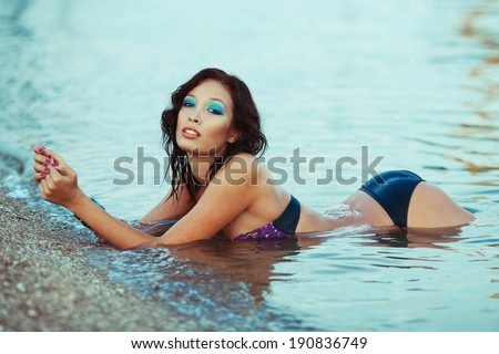Luxurious vacation concept. Beautiful and glamorous young model in bikini on the sunny tropical beach relaxing in water. Wet long curly black hair and perfect waterproof make-up. Outdoor shot - stock photo