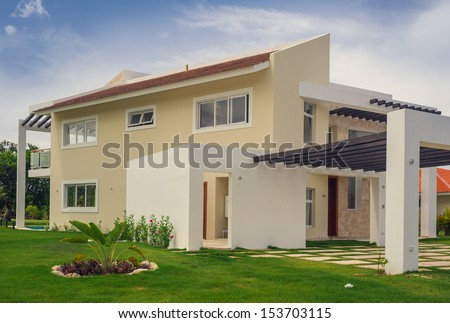 Luxurious villa in Dominican Republic. Beautiful villa with an own swimming pool. villa on luxury Caribbean resort with beautiful garden. Classical spanish villa among flowers, not far from ocean. - stock photo