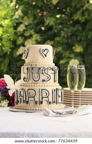 Luxurious wedding cake and two champagne flute glasses on the reception desk - stock photo