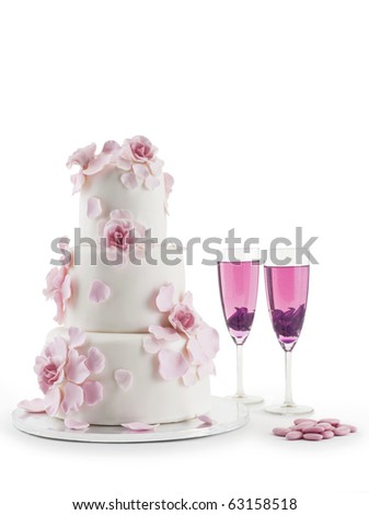 Luxurious wedding cake with flowers and two champagne flute glasses with cocktails; isolated white studio background with copy space. - stock photo