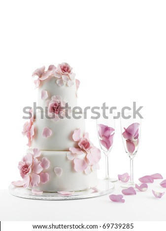 Luxurious wedding cake with flowers and two champagne flute glasses with rose petals;isolated white studio background with copy space. - stock photo