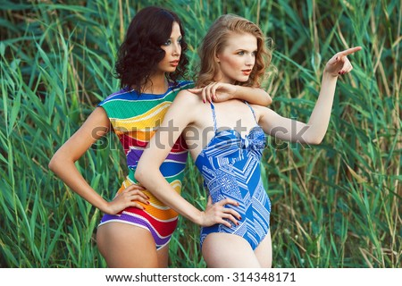 Luxurious weekend concept. Portrait of two gorgeous women (girlfriends) in trendy colorful swimsuits posing on beach. Disco (70s vintage) style. Arty waterproof make-up. Sunny summer day. Outdoor shot - stock photo