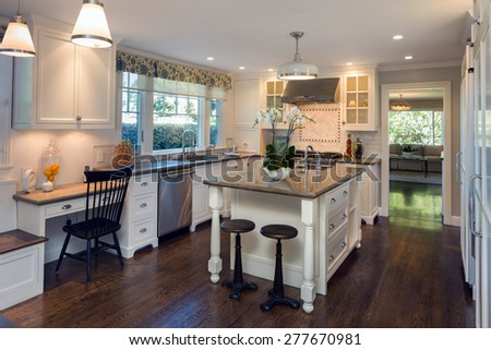 Luxurious white Kitchen in Modern Home with granite counter tops wooden floor, kitchen island with bar stools and all new new stainless steel appliances. - stock photo