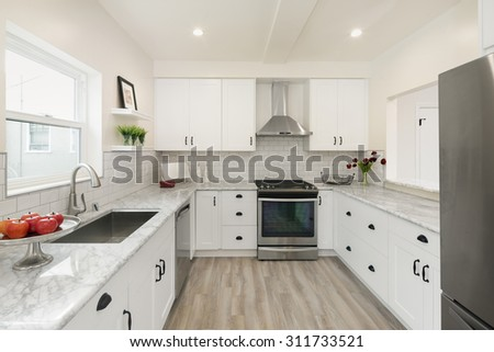 Luxurious white Kitchen in Modern Home with pearl white marble counter tops wooden floor and all new new stainless steel appliances. - stock photo