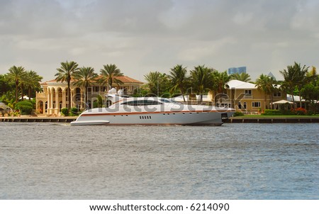 Luxurious yacht docked behind mansion - stock photo