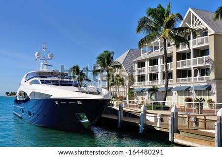 Luxurious Yacht Docked In Front Of Tropical Waterfront Condominiums - stock photo