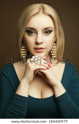 Luxury accessories concept. Portrait of a gorgeous young woman in blue dress with deep decollete wearing luxurious earrings and ring. Close up. Studio shot - stock photo