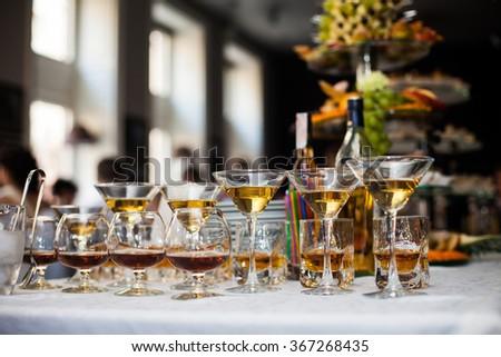 Luxury alcohol wedding table arrangement: cognac, wine and scotch - stock photo