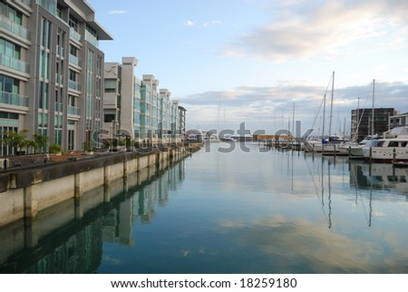 luxury apartment with reflection in water at dawn - stock photo