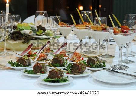 Luxury banquet table setting in restaurant. Table with the wineglasses, snacks and cocktails. - stock photo