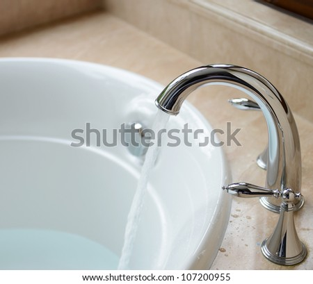 Luxury bath tub and faucet with water. - stock photo