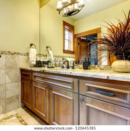 Luxury bathroom cabinets in mountain home with stone tile.
