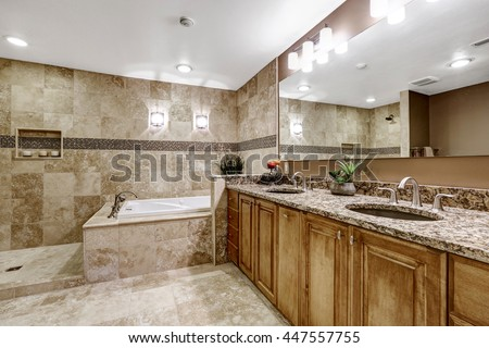 Luxury bathroom interior with tile floor. Bath tub with brown granite tile trim and vanity cabinet with large mirror.