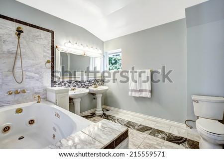 Luxury bathroom interior with tile trim and whirlpool bath tub - stock photo