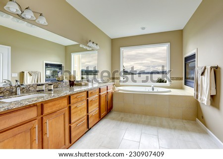 Luxury bathroom with fireplace and bay view.  Brown vanity cabinet with granite top and mirror - stock photo