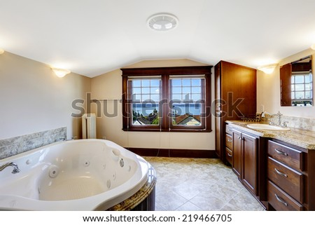 Luxury bathroom with whirlpool, brown cabinet and white whirlpool bath tub - stock photo