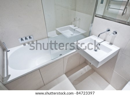 luxury bathroom with white suite and glass screen - stock photo