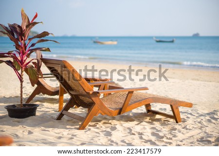 Luxury beach chairs on tropical island beach - stock photo