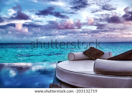 Luxury beach resort, beautiful cozy white lounger near pool, perfect place for honeymoon, gorgeous seascape in overcast weather, summer vacation concept  - stock photo