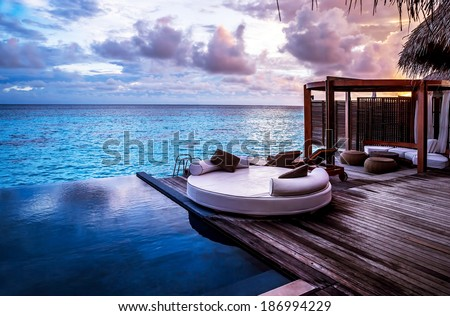 Luxury beach resort, bungalow near endless pool over sea sunset, evening on tropical island, summer vacation concept - stock photo