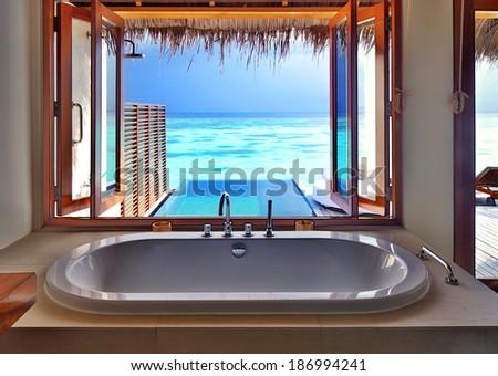 Luxury beautiful interior design on beach resort, window view from bathroom on clear blue sea, summer vacation on Maldives - stock photo