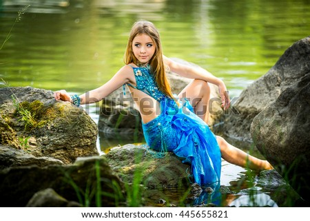 Luxury beautiful young girl in a suit of blue mermaid sitting on a rock by the river waiting for a loved one