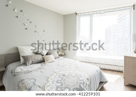 Luxury bedroom. Contemporary design with butterflies on the wall, pillows. Nice and cozy accommodations. Hotel or resort room.  - stock photo