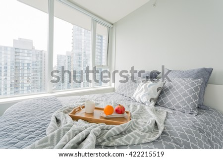 Luxury bedroom. Contemporary design with reclaimed wood bedside tables and lamp. Nice and cozy accommodations. Hotel or resort room. Vancouver downtown view. - stock photo