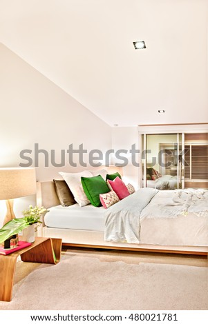 Luxury bedroom illuminated at night with the door entrance to inside which has a wooden table lamps and flower blankets on the bed with pillows
