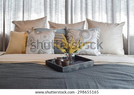 luxury bedroom interior design with striped pillows and decorative tea set on bed - stock photo