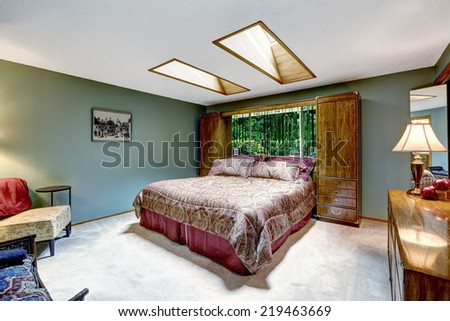 Luxury bedroom interior with burgundy bed and storage combination. Vanity cabinet with lamp