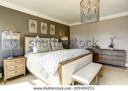 Luxury bedroom interior with carved wood bed, dresser and nightstands - stock photo