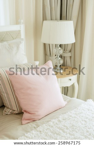 luxury bedroom interior with pink pillows and reading lamp on bedside table - stock photo
