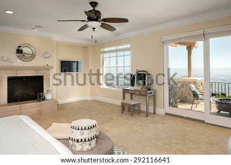 Luxury bedroom interior with rich furniture and scenic view with fire place and ceiling fan. - stock photo