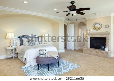 Luxury bedroom interior with rich furniture, fire place and ceiling fan. - stock photo