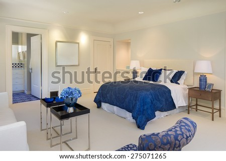 Luxury bedroom with deep blue tones with matching deep blue duvet cover, chair and decoration. - stock photo