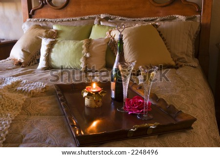 luxury bedroom with pillows and tray with champagne and candle - stock photo