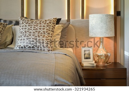 luxury bedroom with white lamp with picture frame on wooden table  - stock photo