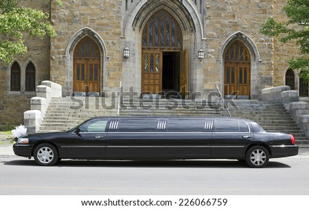 Luxury black limousine awaiting in front of a church - stock photo