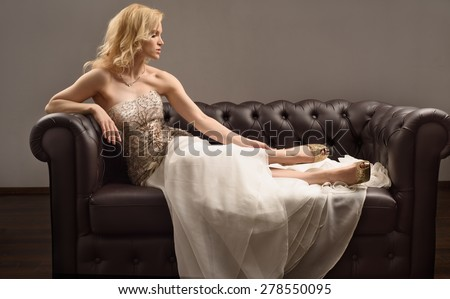 Luxury blonde woman posing on sofa. High resolution - stock photo