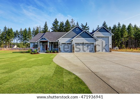 Luxury blue house with curb appeal. Three car garage and long, wide asphalt driveway. Northwest, USA