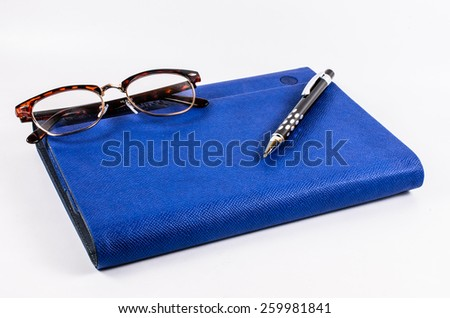 Luxury blue leather organizer  with pen and glasses - stock photo