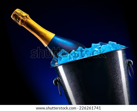 luxury bottle of champagne in Metal ice bucket with ice cubes - stock photo