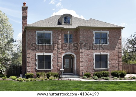 Luxury brick home in suburbs with arched entry - stock photo