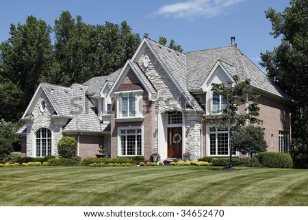Luxury brick home in suburbs with cedar shake roof - stock photo