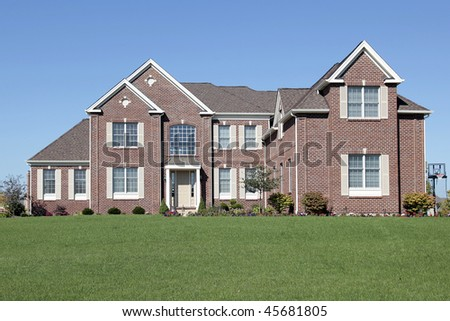 Luxury brick home in suburbs with large front lawn